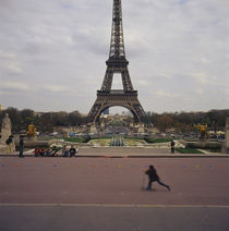 Side profile of a boy riding a push scooter, Eiffel Tower, Paris, France by Panoramic Images