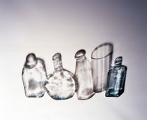 Three clear bottles one clear vase and one blue bottle standing side by side by Panoramic Images