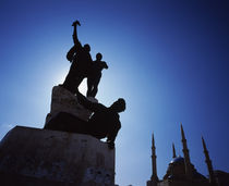 Silhouette of statues with a mosque in the background by Panoramic Images