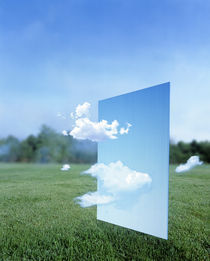 White clouds passing through a pale blue horizontal of sky with green grass by Panoramic Images