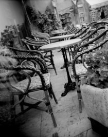 Empty chairs and tables in a sidewalk cafe by Panoramic Images