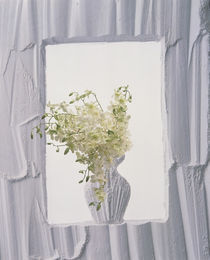 White plaster frame with white plaster vase in center filled with white flowers by Panoramic Images