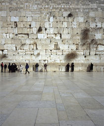 Group of people praying in front of a wall by Panoramic Images