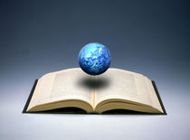 Small cloud filled globe hovering above open book by Panoramic Images