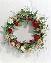 Wreath of pink, red and white roses and green vines on white wall von Panoramic Images