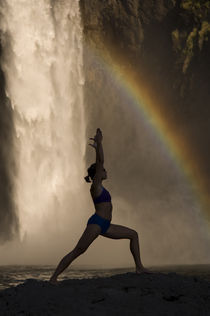 Young woman practicing yoga on a rock, Snoqualmie Falls, Washington State, USA by Panoramic Images