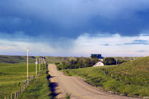 Dirt road through hilly farmland, distant storm, Missouri Breaks, Montana, USA. by Panoramic Images