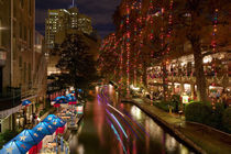 Restaurant along a river lit up at dusk von Panoramic Images