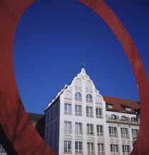 Low angle view of a building through a red circular sculpture von Panoramic Images