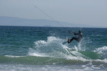 Kite surfer jumping over a wave, Playa de los Lances, Tarifa, Spain.