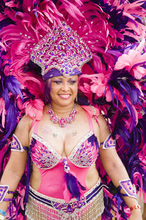 Woman in a pink and purple feathered costume in the Port of Spain carnival in Trinidad. by Tom Hanslien