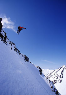Snowboarder jumping into the air. by Ross Woodhall