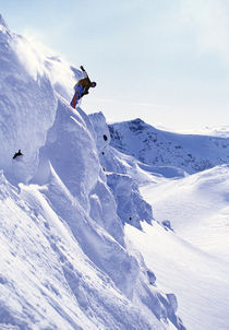 Snowboarder jumping off a mountainside. von Ross Woodhall