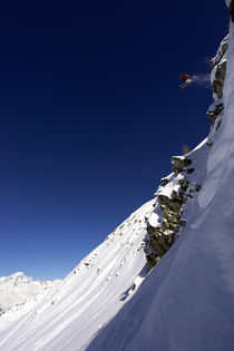 Skier jumping off a cliff. by Ross Woodhall