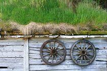 Speichenräder aus Holz an einer Holzhütte mit Dach von fotodil