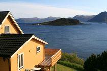 Holzhaus mit Balkon am Wasser von fotodil