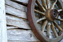 Wagenrad aus Holz an einer Wand aus Brettern by fotodil