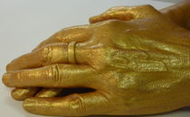 Frauenhände in Gold ruhend von regenbogenfloh