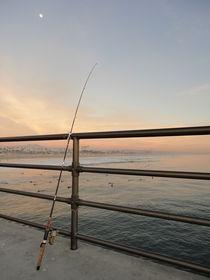 Angelrute lehnt am Geländer eines Pier von Willy Matheisl