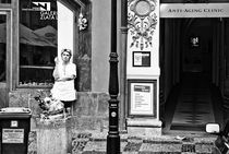 Woman smokes near the entrance to the anti-aging clinic. by Rodion Kovenkin