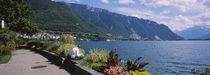 Rear view of a man sitting at the lakeside, Lake Geneva, Montreux, Switzerland by Panoramic Images