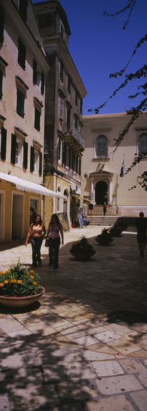 Two women walking in front of a courtyard in Corfu Old Town, Corfu, Greece by Panoramic Images