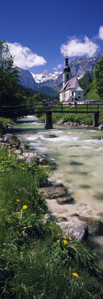 Bridge over stream below country church, Bavarian Alps, Germany. by Panoramic Images