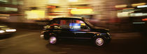 England, London, Black cab in the night by Panoramic Images