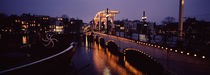 Bridge lit up at night, Magere Brug, Amsterdam, Netherlands by Panoramic Images