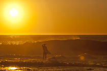 Ein Surfer am Riff von Jakes Point in Westaustralien im Sonnenuntergang by Andy Fox