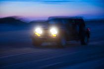 SUV riding off road at night. von John Greim