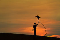 Silhouette of a child flying a kite. by John Greim