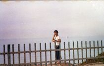 Girl Behind Fence at the Sea Eating Ice Cream by sannekurz