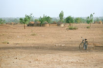 Bicycle and houses outside Béguédo, Burkina Faso by Palle Smith-Petersen