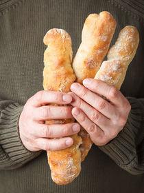 Mann hält französische Baguettes by Elisabeth Cölfen