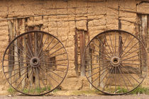 Old wagon wheels in front of mud-brick barn by Danita Delimont