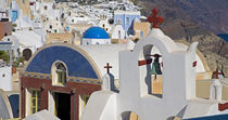 Greece and Greek Island of Santorini town of Oia with Blue Domed Churches with white and colorful buidling surrounding them with the bell tower in the foreground von Danita Delimont