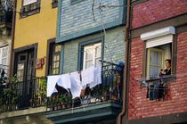 Woman hanging laundry from window in the historic riverside Ribeira district von Danita Delimont