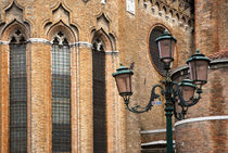 Italy - A lamp post is standing outside an old brick church von Danita Delimont