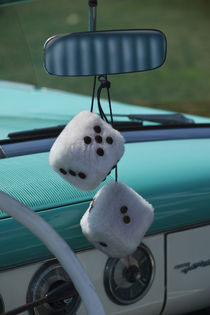 Fuzzy dice in a 1950s-era convertible by Danita Delimont