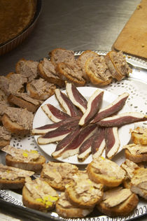 Duck appetizers: dried duck breast and small canapes pieces of bread with duck rillette Ferme de Biorne duck and fowl farm Dordogne France by Danita Delimont