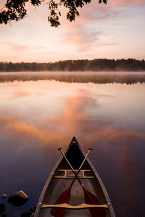 A canoe rests on the shore of Pawtuckaway Lake at dawn as seen from Horse Island in New Hampshire's Pawtuckaway State Park by Danita Delimont
