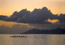 An outrigger canoe team practices off the coast of the island of Tahiti as the sun sets over the island of Moorea in the Society Islands of French Polynesia von Danita Delimont