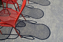 Red wire chairs shadows on concrete by Danita Delimont