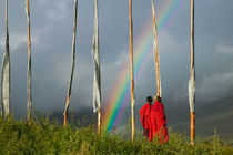 Rainbow over two monks with praying flags in the Phobjikha Valley (MR) by Danita Delimont