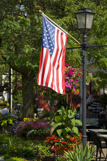 American flag attached to lamp post near wine shop by Danita Delimont