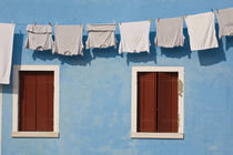 Hanging laundry and windows along blue wall by Danita Delimont