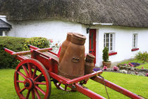 Metal containers on cart and thatched roof cottage von Danita Delimont
