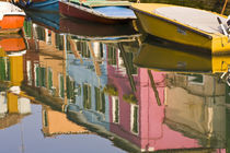 Boats on a canal with reflections of colorful houses on the water von Danita Delimont