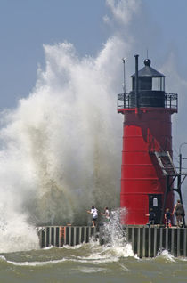 People on jetty watch large breaking waves in South Haven Michigan von Danita Delimont